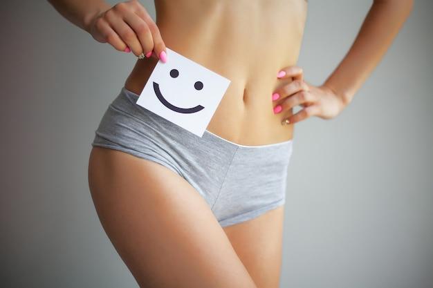 Femme tenant une carte blanche avec un sourire heureux dans ses mains