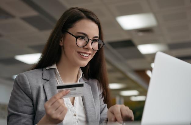 Femme tenant une carte de crédit, achats en ligne, réservation de billets sur le site web