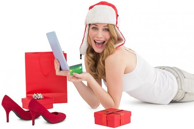 Femme tenant une carte de crédit entourée de cadeaux