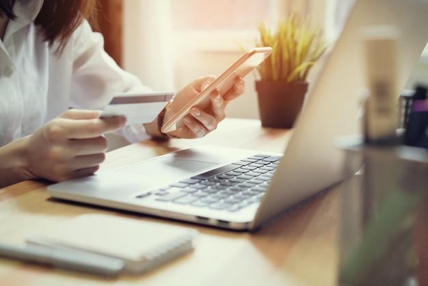 Femme tenant une carte de crédit payer en ligne et en utilisant un smartphone pour faire des achats sur le site web.