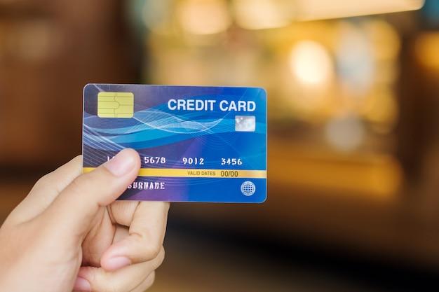 Femme tenant une carte de crédit pour faire du shopping