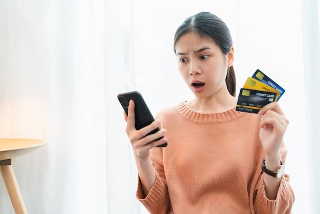 Femme tenant une carte de crédit et un smartphone