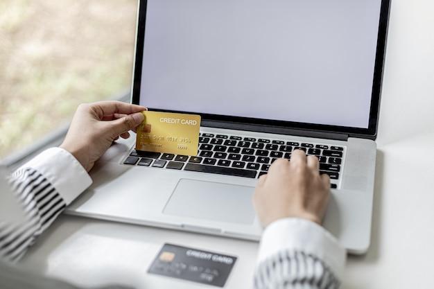 Femme tenant une carte de crédit et tapant sur un clavier d'ordinateur portable, elle remplit les informations de carte de crédit pour payer une commande sur un site d'achat sur internet. concept d'achat en ligne et de paiement par carte de crédit