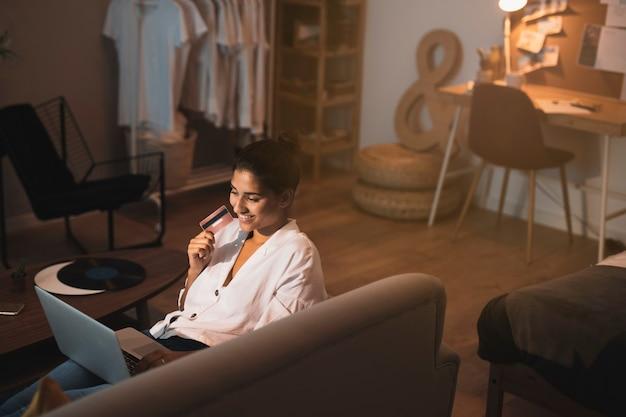 Femme tenant une carte de crédit et travaillant à la maison
