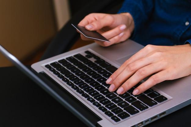 Femme tenant une carte de crédit et utilisant un ordinateur portable pour faire des achats en ligne