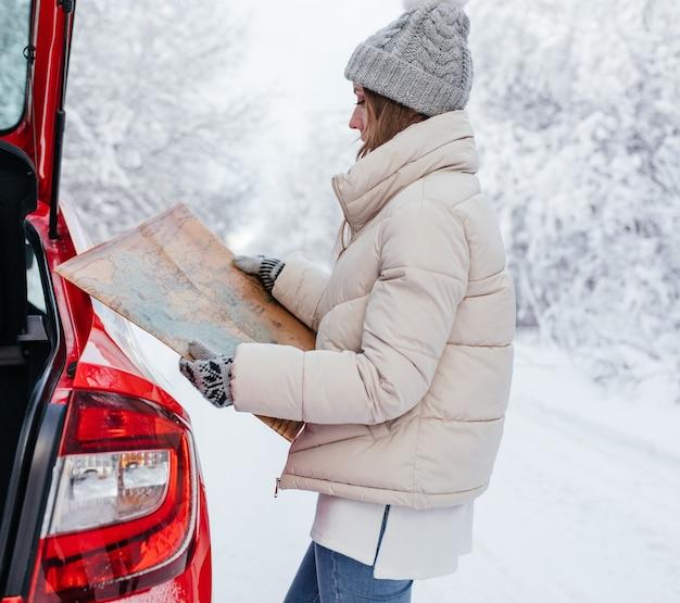 Femme tenant une carte dans ses mains lors de la recherche d'un itinéraire sur le bord de la route dans la forêt d'hiver