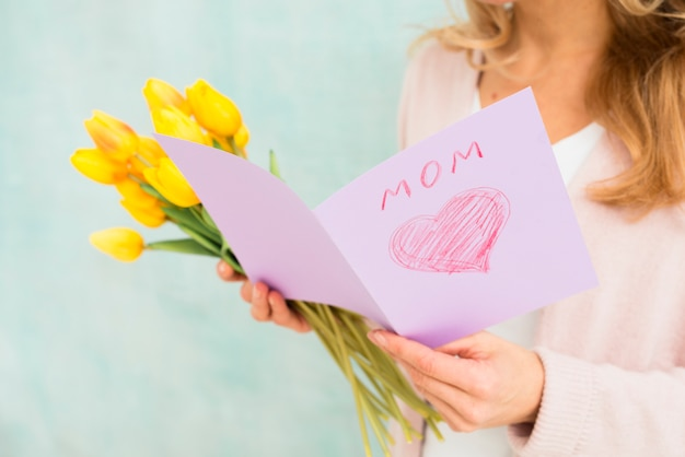 Femme tenant une carte postale et des tulipes