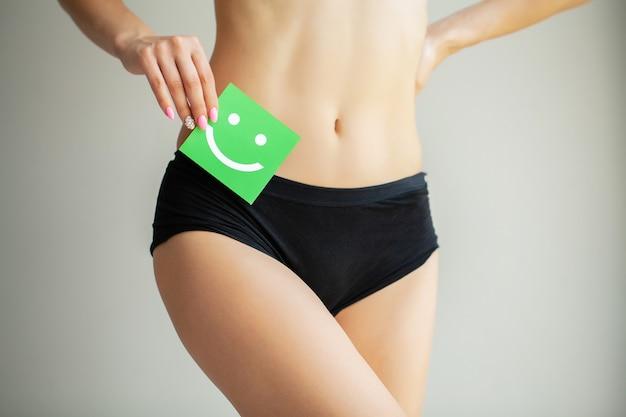 Femme tenant une carte verte avec un sourire heureux dans ses mains