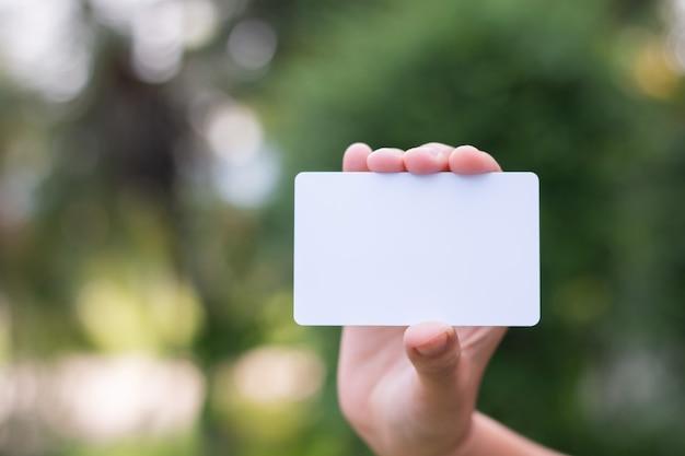 Femme tenant une carte de visite blanche sur fond de bokeh naturel