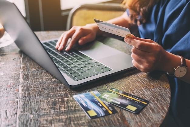 Une femme tenant des cartes de crédit tout en utilisant un ordinateur portable