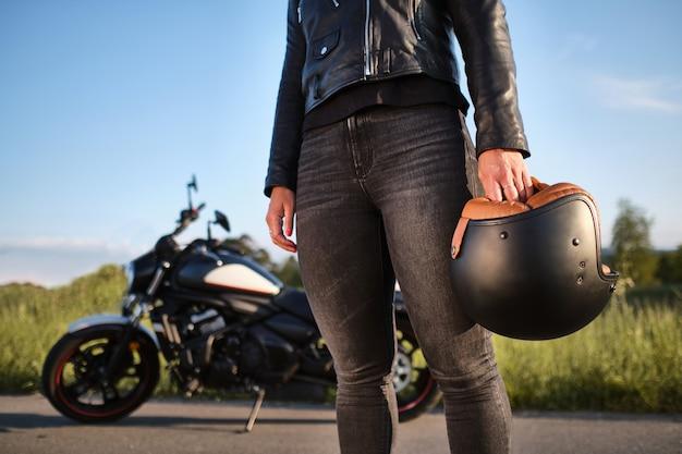 Femme tenant un casque devant un casque de moto