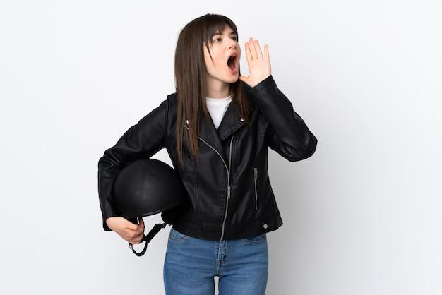 Femme tenant un casque de moto isolé sur blanc en criant avec la bouche grande ouverte
