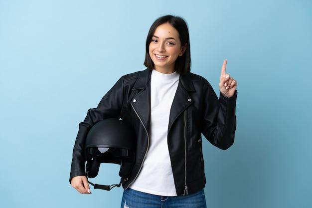 Femme tenant un casque de moto isolé sur bleu pointant vers le haut une excellente idée