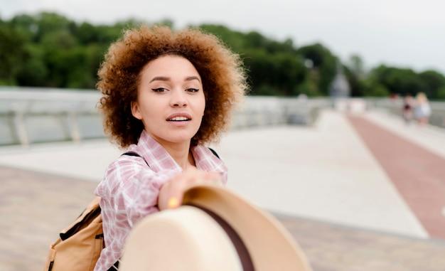 Femme tenant un chapeau devant elle