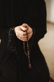 Femme tenant un chapelet et priant