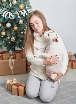 Femme tenant un chien près de coffrets cadeaux et arbre de noël