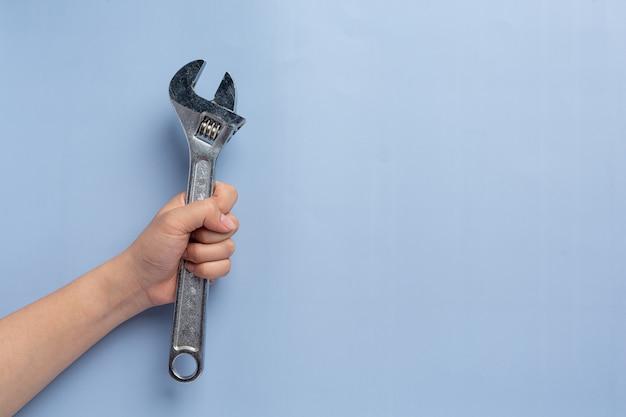 Femme tenant une clé en métal, concept de fond de la fête du travail