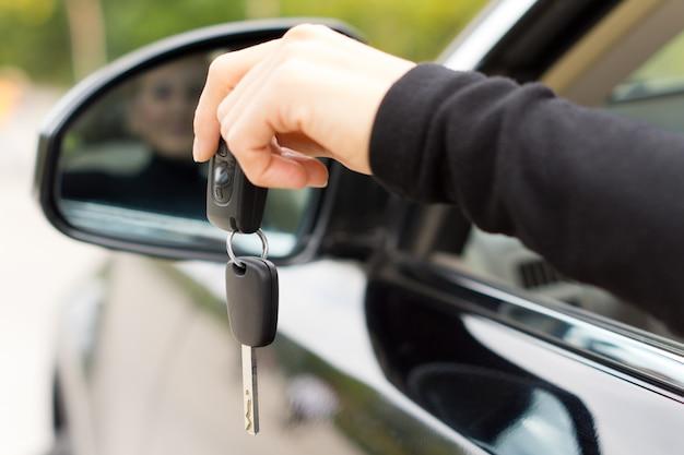 Femme tenant les clés de contact d'une voiture