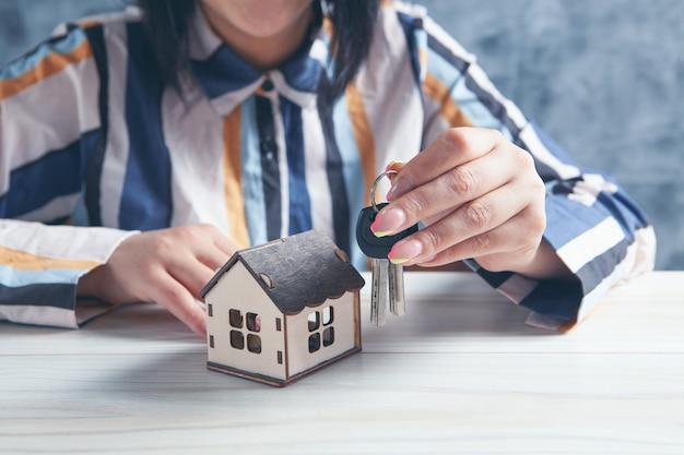 Femme tenant des clés et maison sur table
