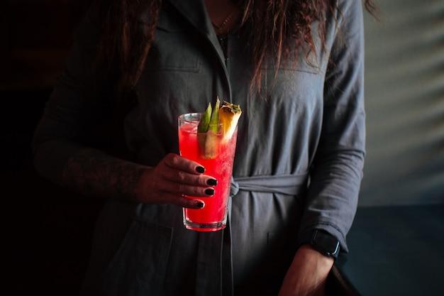 Femme tenant un cocktail rouge dans un highball avec de la glace et de l'ananas