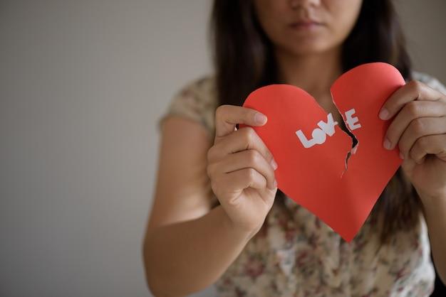 Femme tenant coeur brisé rouge avec texte d'amour. concept de saint valentin