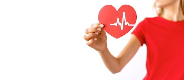 Femme tenant coeur de papier avec espace copie et rythme cardiaque
