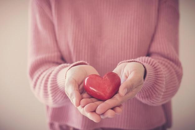 Femme tenant un coeur rouge, assurance maladie, concept de don, journée mondiale de la santé mentale, journée mondiale du cœur