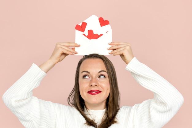 Femme tenant des coeurs de papier enveloppe rouge