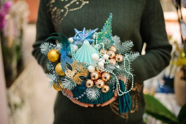 Femme tenant une composition de noël dans un style marin en sapin, boules de verre, coquillage, étoile de mer, masque et perles