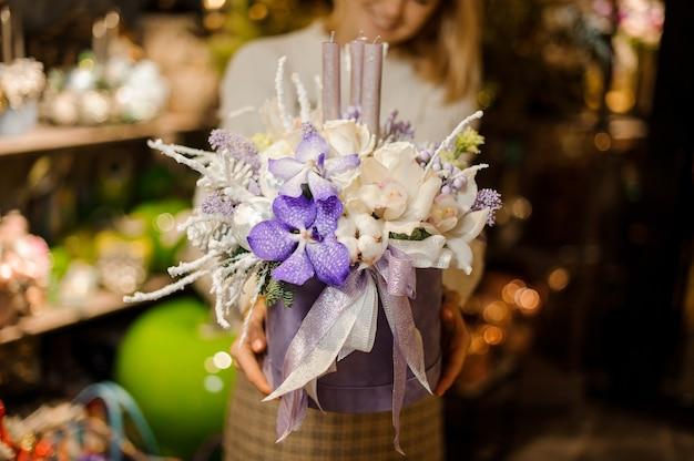 Femme tenant une composition de noël avec des orchidées violettes et blanches et des roses