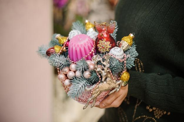Femme tenant une composition de noël en sapin, boules de verre colorées et jouets