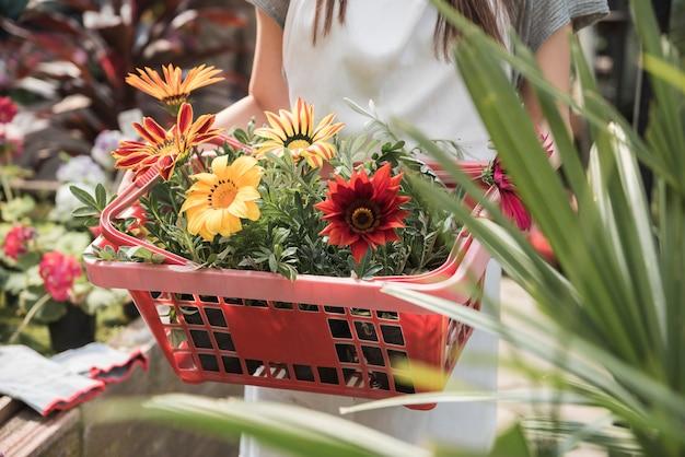 Femme tenant un conteneur avec des fleurs jaunes et rouges