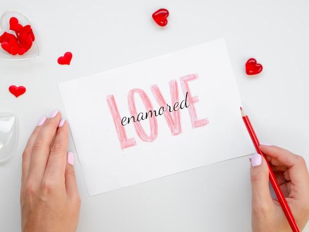 Femme tenant un crayon et un papier d'amour