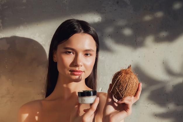 Femme tenant de la crème cosmétique et de la noix de coco à appliquer sur la peau du visage. femme tenir la crème sur le vieux fond de mur à l'ombre du feuillage. concept publicitaire de mode de vie sain, spa et soins personnels