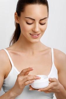 Femme tenant la crème cosmétique
