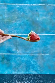 Femme tenant une cuillère de fraise sur une surface bleue