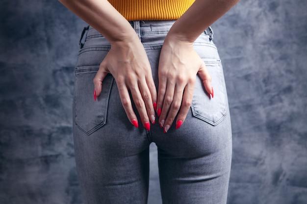 Femme tenant le cul. notion d'hémorroïdes