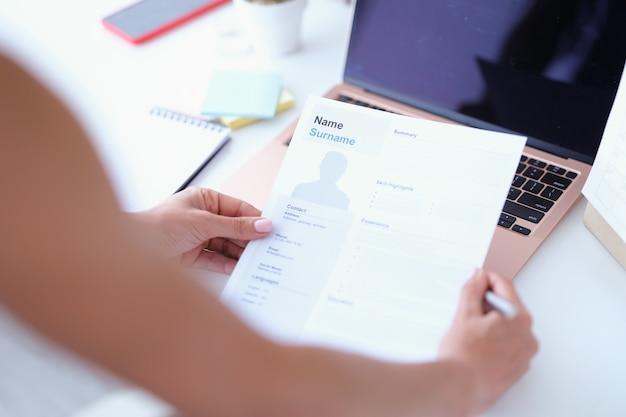 Femme tenant un curriculum vitae pour un emploi dans ses mains devant un ordinateur portable en gros plan