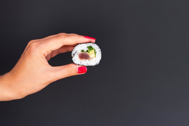 Femme tenant dans la main un morceau de rouleau de sushi