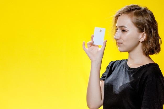 Femme tenant dans les mains démontrant la nouveauté de la carte bancaire sur fond jaune.