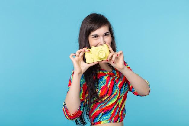 Femme tenant dans ses mains un appareil photo vintage jaune