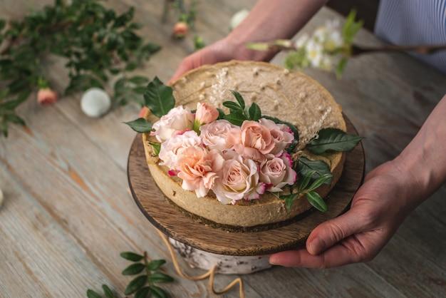 Femme tenant dans ses mains un beau gâteau mousse crue décoré de fleurs de tendresse