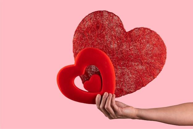 Femme tenant dans ses mains deux coeurs. concept de la saint-valentin