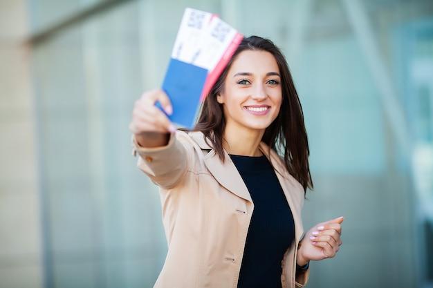 Femme tenant deux billets d'avion dans un passeport à l'étranger près de l'aéroport