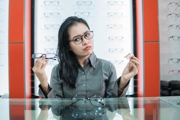 Une femme tenant deux lunettes est confuse quant au choix d'une nouvelle paire de lunettes chez un opticien
