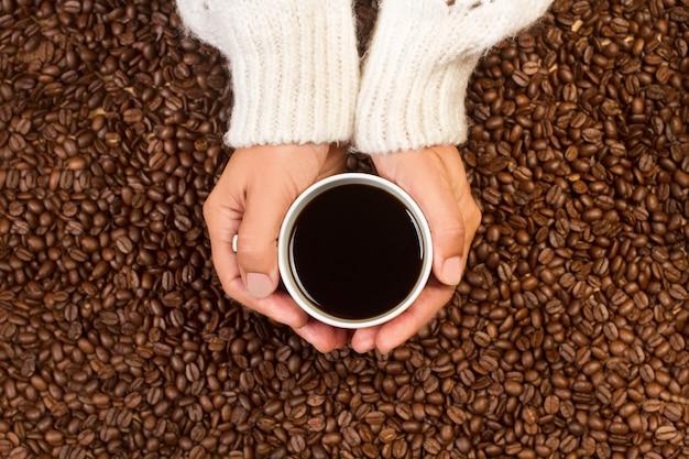 Femme tenant à deux mains une tasse de café noir sur un tas de grains de café en vue de dessus