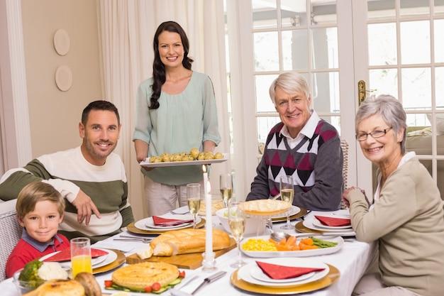 Femme tenant le dîner de noël avec la famille à la table à manger