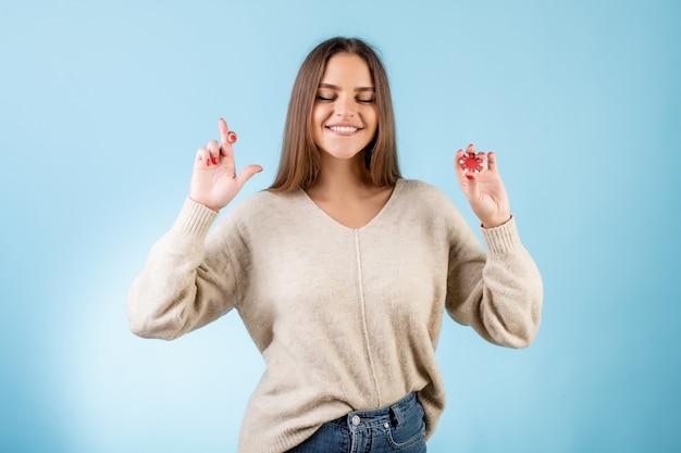 Femme tenant les doigts croisés pour la chance et jeton de poker rouge isolé sur bleu