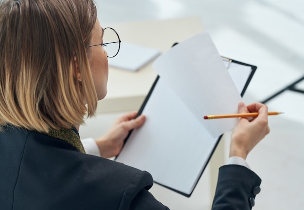 Femme tenant un dossier avec une feuille de papier blanc gros plan