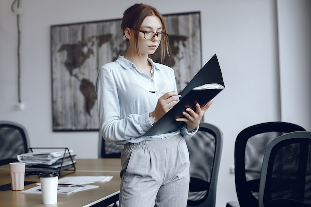 Femme tenant un dossier fille signe les documents. beauté à lunettes.